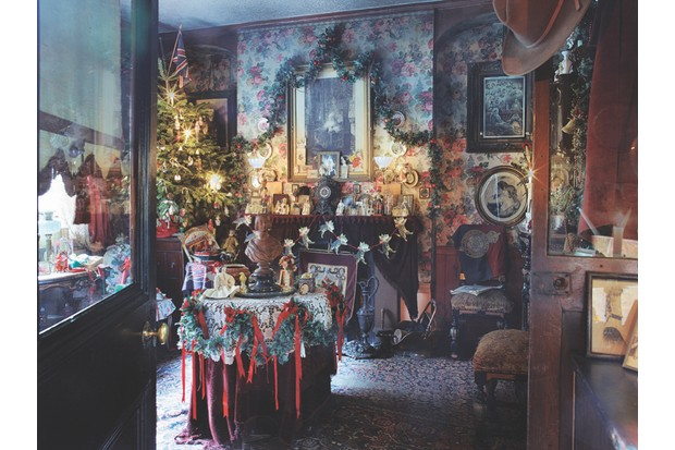 The Victorian parlour in Dennis Severs' House featuring a large real Christmas trees, ribbon garland and bold floral wallpaper