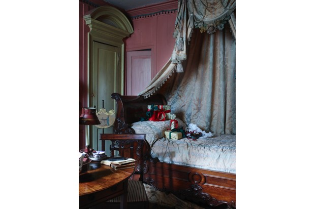 A bedroom in Dennis Severs' House with a mahogany single bed swathed in a damask-printed canopy