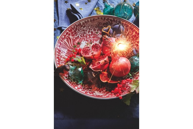 A red and white William de Morgan charger holds festive fruits and joyful sparklers
