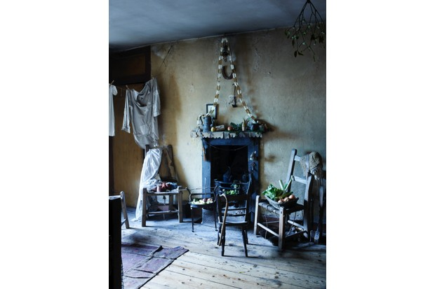 The attic bedroom in Dennis Severs' House. Simple wooden chairs surround a blackened fireplace and laundry hangs to dry