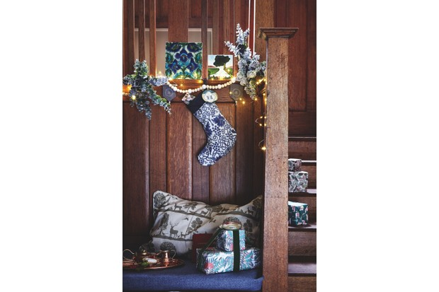 Arts and crafts staircase decorated with blue and white decorations. Morris & Co fabric is used to create a stocking. Eucalyptus stems are used as foliage to decorate the stairs