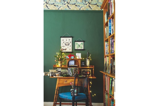 An office is decorated using William Morris wallpaper against a festive green wall. Vintage wall charts are hung above a liberty desk.