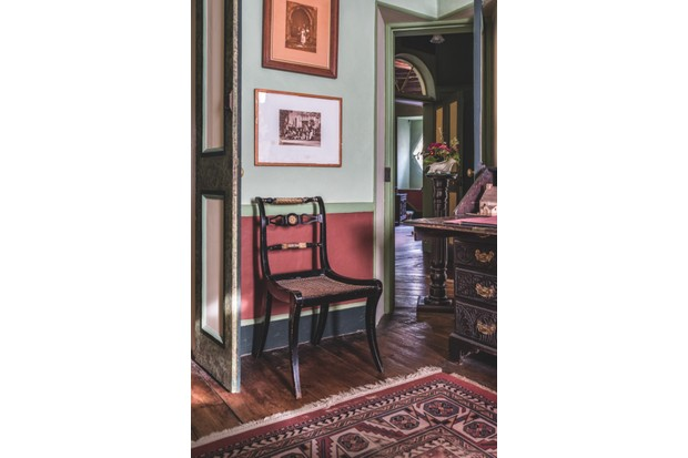 The Music Room in A La Ronde, with bold red wallpaper and an ornate black desk and chair