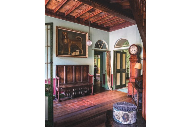 The Entrance Hall in A La Ronde with pale green walls, a large antique bench and a striking oil painting of a dog