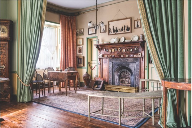 The Drawing Room in A La Ronde with long green velvet curtains, a large Persian rug and an ornamental fireplace