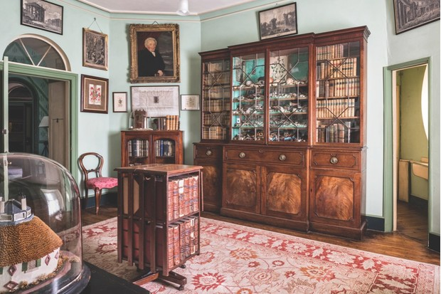 The Library at A La Ronde with a large mahogany bookcase filled with antique books and curios. The walls are lined with portraits and paintings.