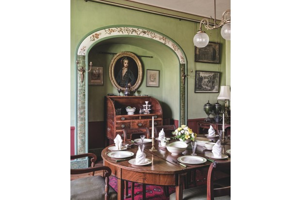 The Dining Room at A La Ronde painted in a rich sage green, with a large mahogany dining table laid for dinner. There's an antique bureau and an oil painting inside a wall alcove.