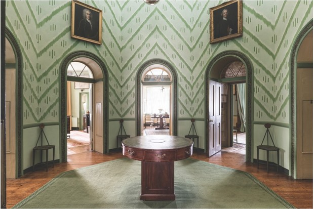 The central Octagon room in A La Ronde clad in green zigzag wallpaper with portraits of men on the walls.