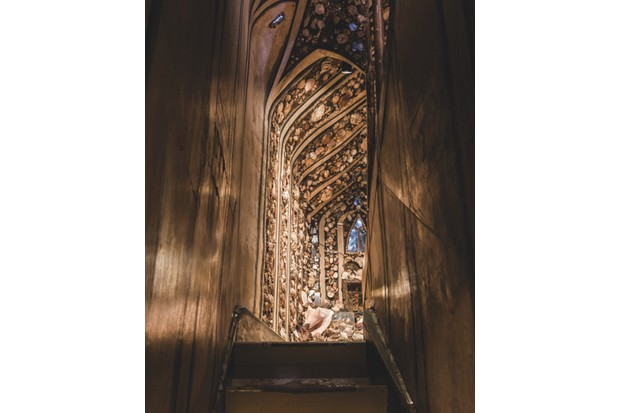 A view up the narrow staircase in the Shell Gallery at A La Ronde. You can see a glimpse of the shell-lined ceiling and tiny ornate windows.