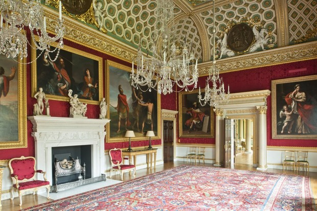 An entrance room in Spencer House. The walls are painted in rich red, and are adorned with large paintings of the hunt.