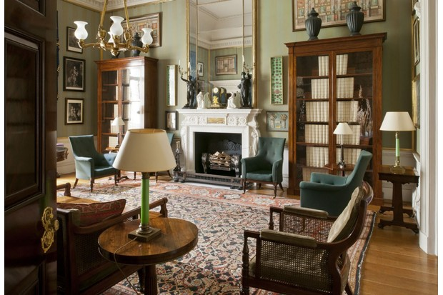 The library in Spencer House features a large stone fireplace, antique wooden bookcases, green armchairs and a large antique rug.