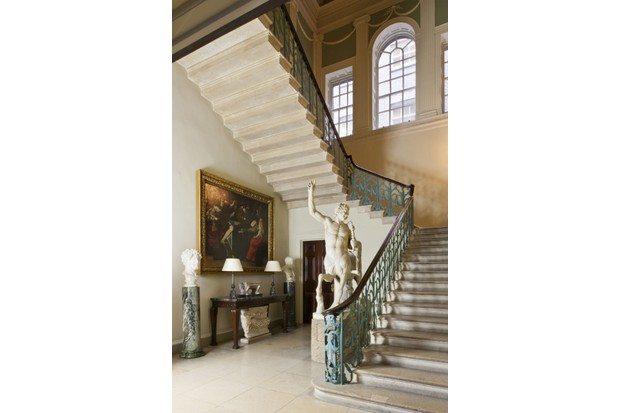 The grand staircase hall in Spencer House, featuring a sweeping stone staircase with an Grecian sculpture at the bottom.