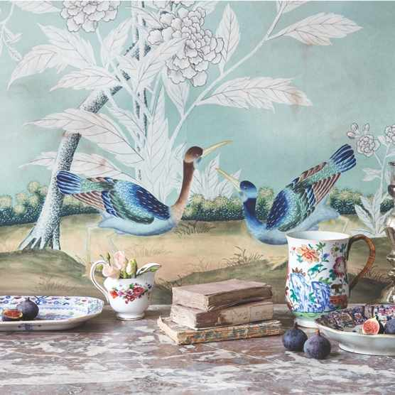 A wallpaper with an image of birds on it gives the backdrop to a range of oriental ceramics