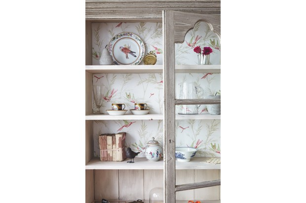 A chinoiserie style wallpaper is the backdrop for a collection of china on top of shelving