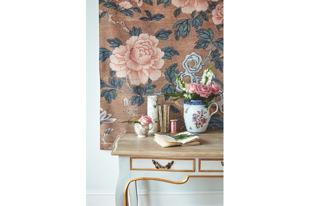A fabric printed wall hanging is being used as the backdrop for an oriental flower pot