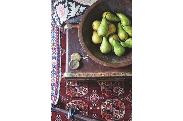 A hardwood bowl filled with pears, resting on a vintage steamer trunk