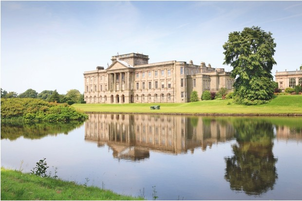 The facade of Cheshire's Lyme Park is reflected in an ornamental lake.