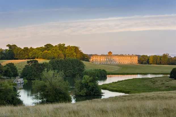 The sun sets over Petworth House in West Sussex and the surrounding ponds and grassland.