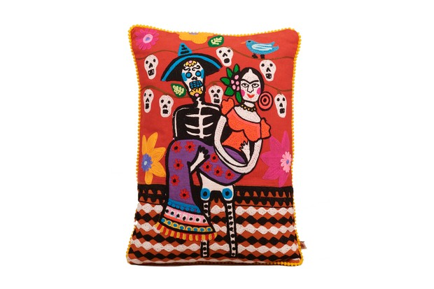 Vibrant and colourful Day of the Dead cushion. A skeleton man holds Frida Kahlo in his arms