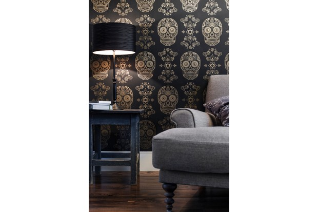 Gold & Black Day of the Dead Wallpaper in a living room setting with a distressed table and beige fabric armchair