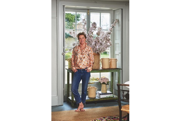 A photo of Nikki Tibbles standing in front of a plant pot inside her home