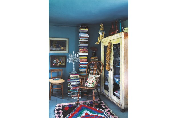 Cookery books are stacked high behind a wooden chair