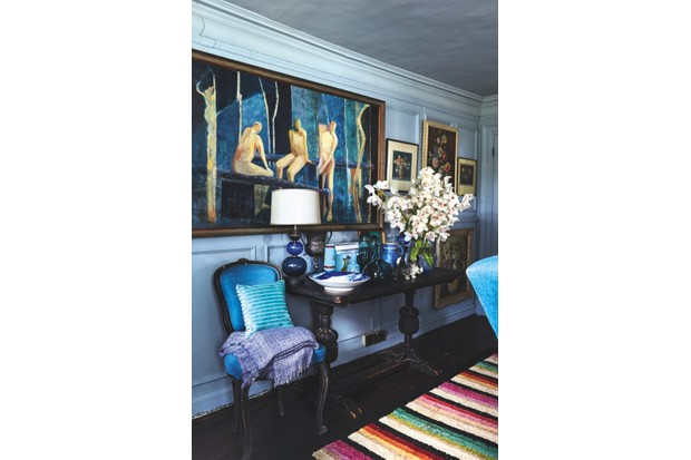 Paintings hang on a wall above a table