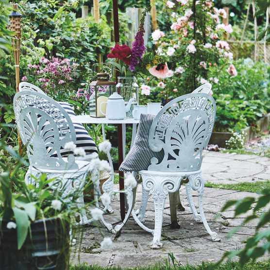 An antique white metal bistro set in a cottage garden in full bloom. Image courtesy Rachel Whiting, Ryland Peters & Small.