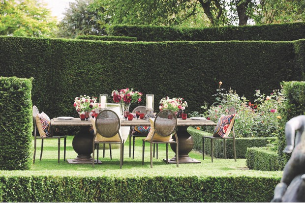 A traditional long table adorned with fresh flowers surrounded by a well-manicured hedge
