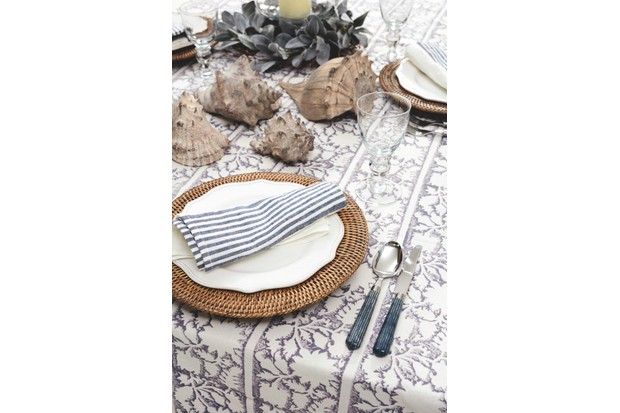 An outdoor dining table decorated with a patterned tablecloth, rattan place settings, striped napkins and decorative sea shells