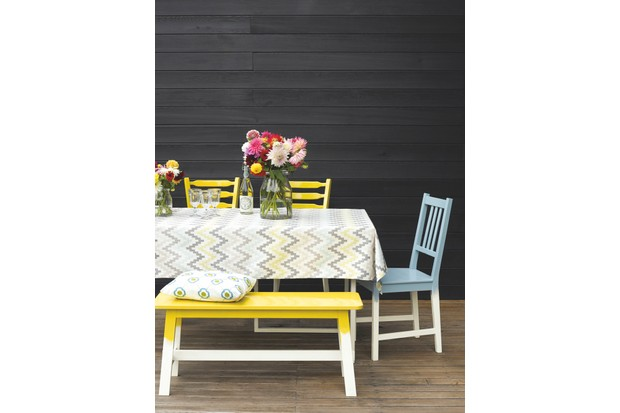 A long table with colourful blue and yellow chairs in front of a dark grey fence