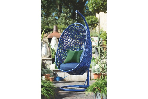 A woven blue hanging chair with dark green cushions