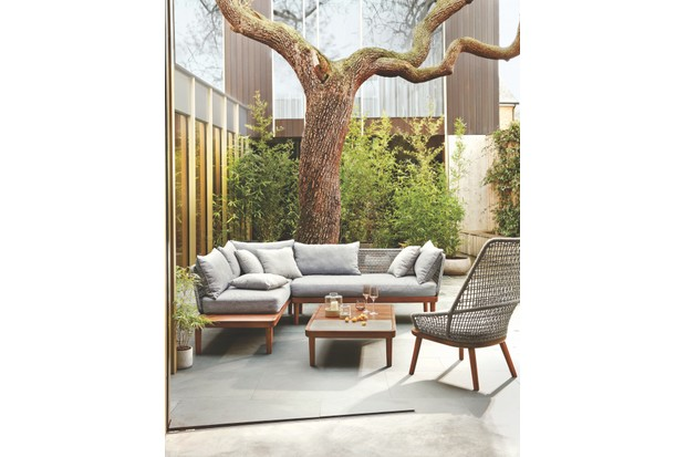 An outdoor seating area compromising of a contemporary corner sofa, low coffee table and woven rattan armchair