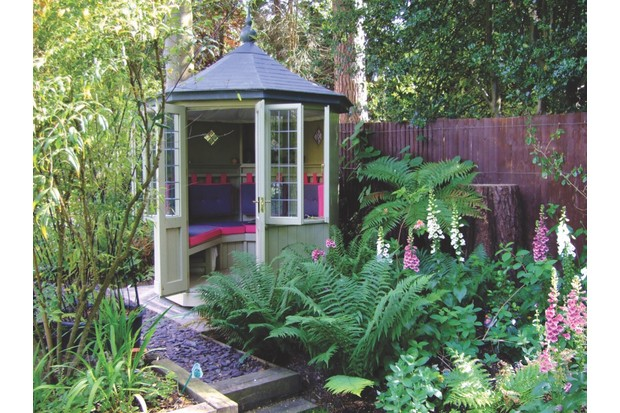 A small round summer house surrounded by ferns and other leafy foliage