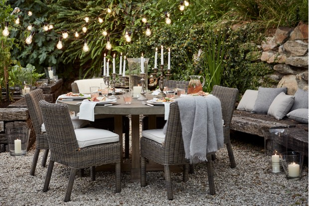 A gravel patio area with wicker chairs and table