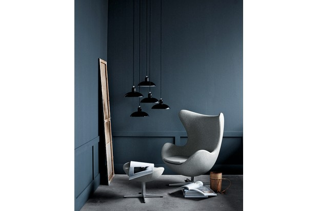 An Egg Chair upholstered in grey fabric against a dark blue wall