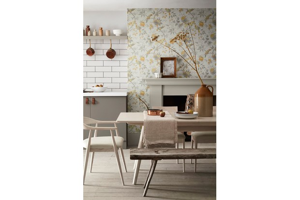 Floral wallpaper used to cover a chimney breast in a shaker-style kitchen