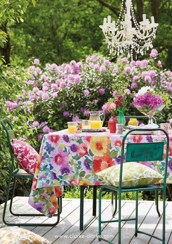 A green metal garden table covered with a bold floral tablecloth