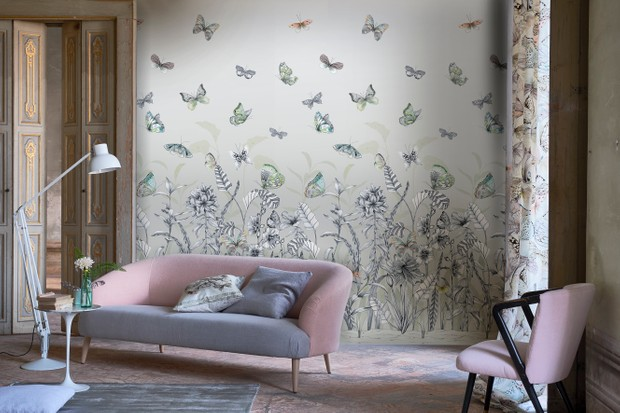 Wallpaper depicting flowers and butterflies is used as a statement wall in a minimal living room
