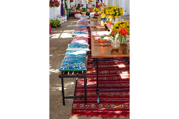 A long wooden and metal table with benched covered in colourful Indian cushions