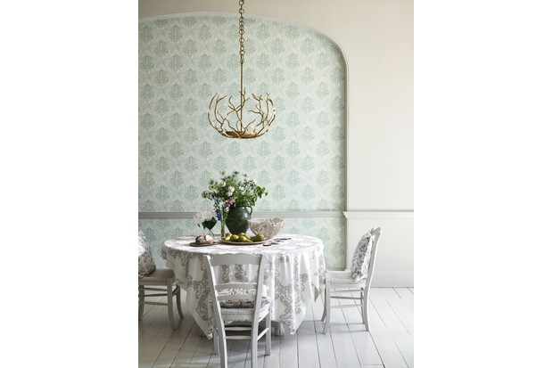 Green, symmetrical wallpaper lines an alcove in a period dining room