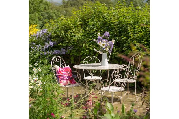 Elegant white metal patio furniture with an enamel vase of wild flowers