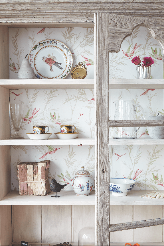 Elegant chinoiserie wallpaper lines the back of an antique dresser displaying vintage crockery and glassware