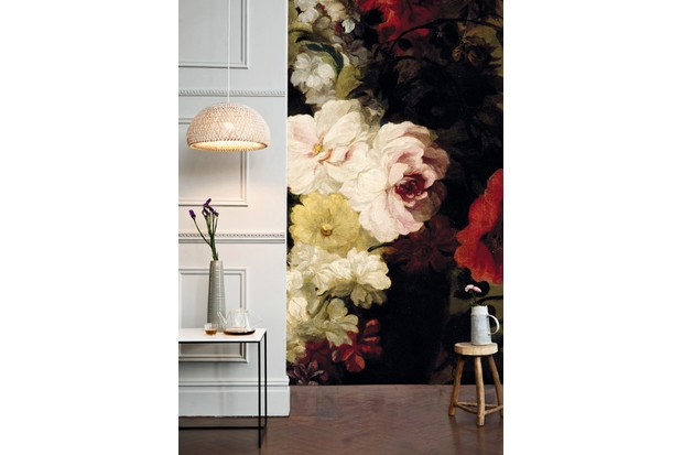 An oversized floral wall mural makes a statement in a moody bedroom