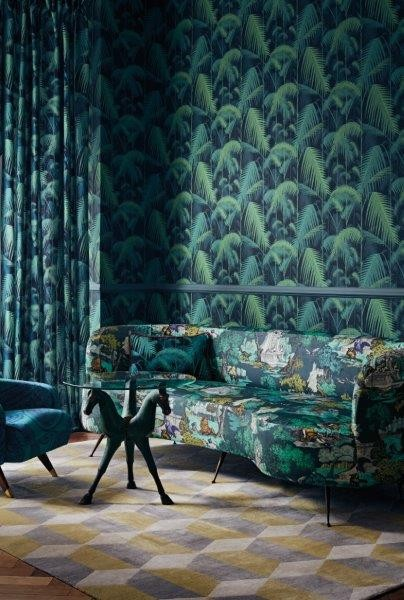 Green palm-leaf wallpaper is used in conjunction with a dark green sofa