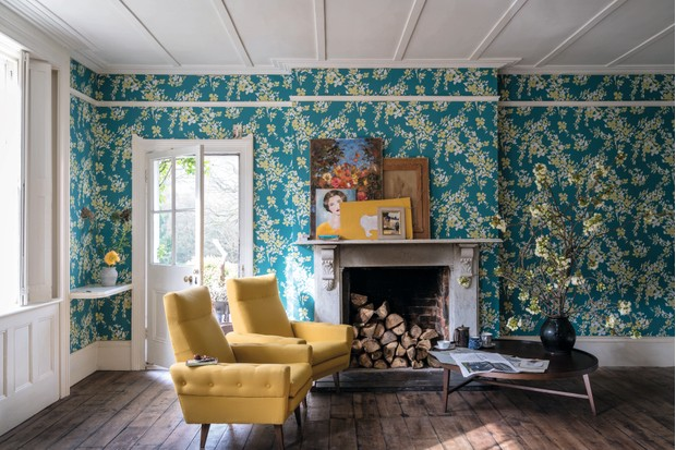 A bold floral design is used to wallpaper every wall in a large living room with yellow armchairs