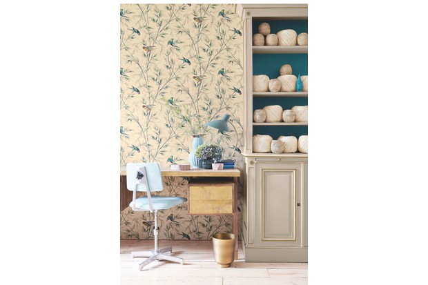 An office space with a desk and distressed dresser wallpapered in floral wallpaper