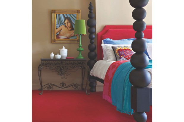 A contemporary four poster bed resting on bright red carpet