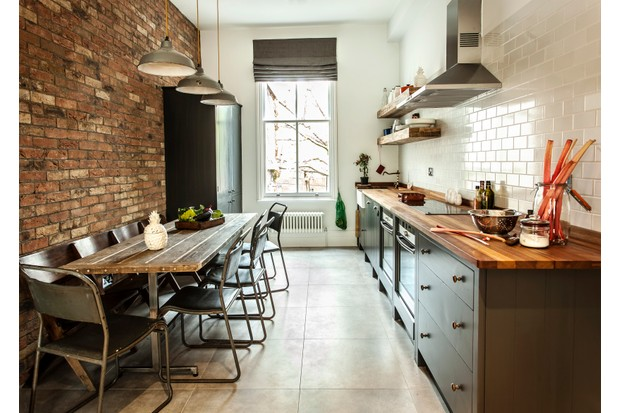 An industrial-style kitchen with and exposed brick wall