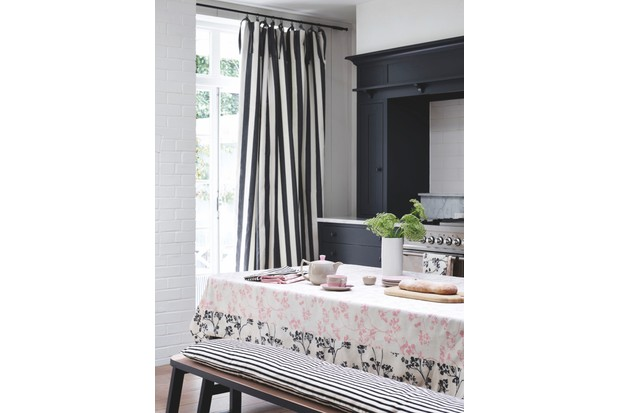A dark blue kitchen with striped curtains and a table covered with a floral tablecloth